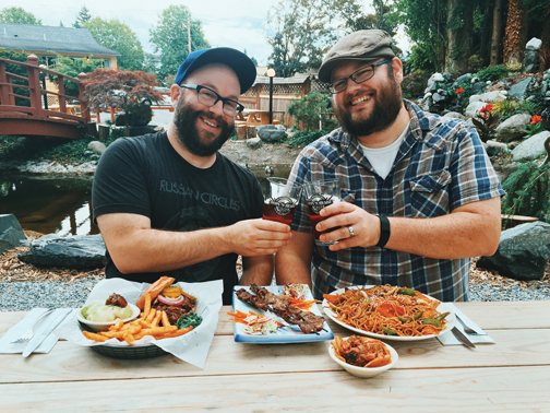 The Aarons enjoy their plates of Galbi skewers, pulled pork, and Yakisoba, in the unique beer garden at Hops 'N Headz. PHOTO BY RYAN RUSSELL